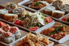 Ανάμεικτα ιαπωνικά πιάτα στα άσπρα τετραγωνικά πιάτα στις ξύλινες στάσεις στο υπόβαθρο του πίνακα στοκ φωτογραφίες
