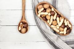 Ανάμεικτα καρύδια: ξύλο καρυδιάς, κάστανο, φυστίκι στο ξύλινο κύπελλο στο μόριο Στοκ εικόνες με δικαίωμα ελεύθερης χρήσης