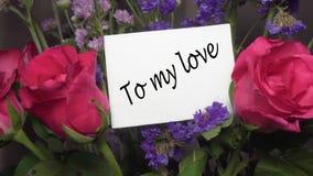"""Ανάμεικτα λουλούδια με τα ρόδινα τριαντάφυλλα με τη ευχετήρια κάρτα τίτλος """"της αγάπης μου """" φιλμ μικρού μήκους"""