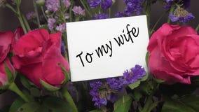 """Ανάμεικτα λουλούδια με τα ρόδινα τριαντάφυλλα με τη ευχετήρια κάρτα τίτλος """"των συζύγων μου """" απόθεμα βίντεο"""