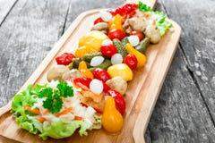 Ανάμεικτα παστωμένα λαχανικά - Sauerkraut λάχανο, πιπέρια, αγγούρια, ντομάτες, κρεμμύδια, μανιτάρια και χορτάρια στον τέμνοντα πί Στοκ Φωτογραφίες