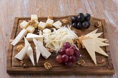 Ανάμεικτα τυριά με τα σταφύλια και ξύλα καρυδιάς σε έναν εξυπηρετώντας πίνακα Στοκ εικόνες με δικαίωμα ελεύθερης χρήσης