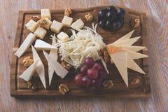 Ανάμεικτα τυριά με τα σταφύλια και ξύλα καρυδιάς σε έναν εξυπηρετώντας πίνακα Στοκ Εικόνες