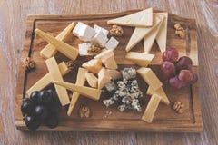 Ανάμεικτα τυριά με τα σταφύλια και ξύλα καρυδιάς σε έναν εξυπηρετώντας πίνακα Στοκ Εικόνα