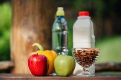Ανάμεικτα φρέσκα λαχανικά, πιπέρια, μήλα, νερό και γάλα στον ξύλινο πίνακα γιόγκα, έννοια ζωής, υγιή τρόφιμα κατανάλωσης Στοκ Εικόνες
