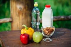 Ανάμεικτα φρέσκα λαχανικά, πιπέρια, μήλα, νερό και γάλα στον ξύλινο πίνακα γιόγκα, έννοια ζωής, υγιή τρόφιμα κατανάλωσης Στοκ Φωτογραφία