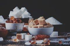 Ανάμεικτοι διαφορετικοί τύποι ζαχαρών στα κύπελλα σε έναν πίνακα σε ένα σκοτάδι στοκ εικόνα