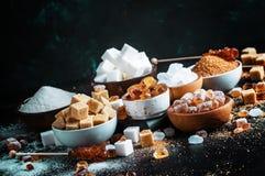 Ανάμεικτοι διαφορετικοί τύποι ζαχαρών στα κύπελλα σε έναν πίνακα σε ένα σκοτάδι στοκ εικόνες