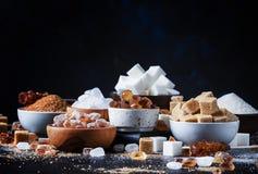 Ανάμεικτοι διαφορετικοί τύποι ζαχαρών στα κύπελλα σε έναν πίνακα σε ένα σκοτάδι στοκ φωτογραφία με δικαίωμα ελεύθερης χρήσης