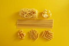 Ανάμεικτοι τύποι ζυμαρικών στο κίτρινο υπόβαθρο στοκ εικόνα