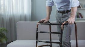 Ανάπηρος άνθρωπος που προσπαθεί να κινηθεί με το πλαίσιο περπατήματος στο νοσοκομείο, αποκατάσταση Στοκ Εικόνες
