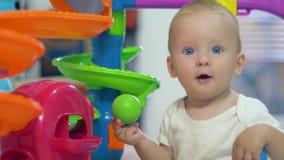 Ανάπτυξη παιδιών, χαριτωμένο νήπιο που παίζεται με τα χρωματισμένα παιχνίδια στο χώρο για παιχνίδη φιλμ μικρού μήκους