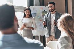 Ανάπτυξη της νέας στρατηγικής Δύο νέοι συνάδελφοι που διευθύνουν το παρόν στοκ εικόνες