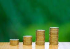 Ανάπτυξη των σωρών νομισμάτων με το πράσινο υπόβαθρο δέντρων bokeh οικονομικός Στοκ εικόνα με δικαίωμα ελεύθερης χρήσης