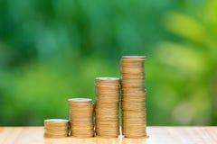 Ανάπτυξη των σωρών νομισμάτων με το πράσινο υπόβαθρο δέντρων bokeh οικονομικός Στοκ Φωτογραφίες