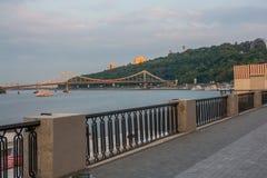 Ανάχωμα που αγνοεί τη για τους πεζούς γέφυρα στο ηλιοβασίλεμα, Ουκρανία, Kyiv εκδοτικός 08 03 2017 Στοκ εικόνα με δικαίωμα ελεύθερης χρήσης