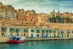 Ανάχωμα Valletta με τις παραδοσιακές ζωηρόχρωμες πόρτες και το δεμένο σκάφος στοκ εικόνα