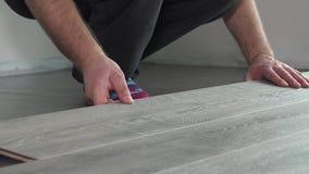 Ανάδοχος που εγκαθιστά το ξύλινο φυλλόμορφο δάπεδο με τη μόνωση απόθεμα βίντεο