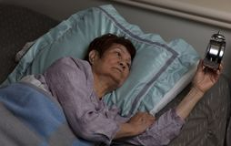 Ανήσυχη ανώτερη γυναίκα που λάμπει στο ξυπνητήρι κατά τη διάρκεια της νύχτας wh στοκ φωτογραφία