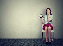Ανήσυχη γυναίκα με το ξυπνητήρι που περιμένει μια συνέντευξη στοκ φωτογραφία με δικαίωμα ελεύθερης χρήσης