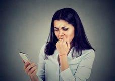 ανήσυχη γυναίκα που προσέχει apps στο κινητό τηλέφωνοη Στοκ εικόνα με δικαίωμα ελεύθερης χρήσης