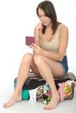Ανήσυχη ενδιαφερόμενη νέα συνεδρίαση γυναικών σε μια ξεχειλίζοντας βαλίτσα που κρατά ένα διαβατήριο ανησυχημένος στοκ εικόνες