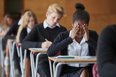 Ανήσυχη εφηβική εξέταση συνεδρίασης σπουδαστών στη σχολική αίθουσα στοκ φωτογραφίες