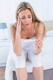 Ανήσυχη ξανθή γυναίκα που φαίνεται η δοκιμή εγκυμοσύνης της στοκ εικόνες