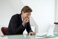 Ανήσυχος επιχειρηματίας που εξετάζει το lap-top Στοκ Εικόνες