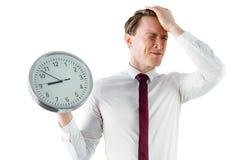 Ανήσυχος επιχειρηματίας που κρατά ένα ρολόι Στοκ Φωτογραφία