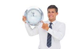 Ανήσυχος επιχειρηματίας που κρατά και που παρουσιάζει ένα ρολόι στοκ φωτογραφίες με δικαίωμα ελεύθερης χρήσης
