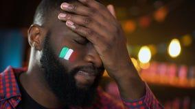 Ανήσυχος μαύρος ανεμιστήρας ποδοσφαίρου την ιταλική σημαία που χρωματίζεται με στο μάγουλο που υφίσταται facepalm την απώλεια απόθεμα βίντεο