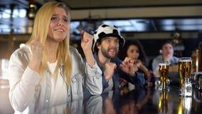 Ανήσυχος ξανθός ανεμιστήρας γυναικείου αθλητισμού που διασχίζει τα δάχτυλα, θεατές που προσέχουν το παιχνίδι στο μπαρ στοκ φωτογραφίες με δικαίωμα ελεύθερης χρήσης