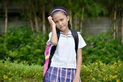 Ανήσυχος σπουδαστής κοριτσιών που φορά τη σχολική στολή με τα βιβλία στοκ εικόνες