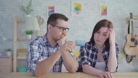 Ανήσυχο ζεύγος με μια συνεδρίαση πιστωτικών καρτών σε έναν πίνακα σε ένα σύγχρονο διαμέρισμα απόθεμα βίντεο