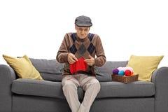 Ανίδεη ανώτερη συνεδρίαση σε έναν καναπέ και πλέξιμο Στοκ Εικόνες
