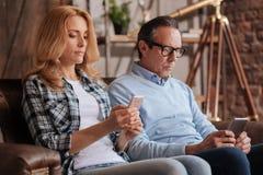 Ανίδεο ζεύγος που χρησιμοποιεί τα κινητά τηλέφωνα στο σπίτι στοκ εικόνες