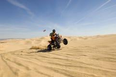 Αναβάτης ποδηλάτων τετραγώνων που κάνει Wheelie στην έρημο Στοκ Εικόνα