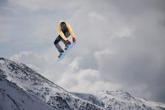 Αναβάτης σνόουμπορντ που πηδά στα βουνά Ακραίος αθλητισμός σνόουμπορντ Στοκ Εικόνες