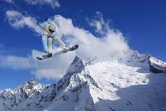 Αναβάτης σνόουμπορντ που πηδά στα βουνά Ακραίος αθλητισμός freeride σνόουμπορντ Στοκ Εικόνα