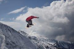 Αναβάτης σνόουμπορντ που πηδά στα βουνά Ακραίος αθλητισμός freeride σνόουμπορντ Στοκ Φωτογραφίες