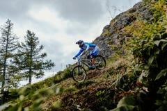 Αναβάτης στο βουνό ποδηλάτων προς τα κάτω και τη δασική διαδρομή Στοκ Εικόνες