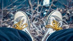 Αναδρομικά καφετιά πάνινα παπούτσια με τα κίτρινα κορδόνια που κρεμούν στην άκρη στοκ φωτογραφία με δικαίωμα ελεύθερης χρήσης