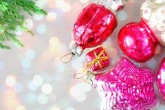 Αναδρομικά παιχνίδια Χριστουγέννων γυαλιού στην ξύλινη επιτροπή στα φω'τα Χριστουγέννων Στοκ Εικόνες