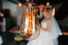 Αναδρομικά φω'τα βολβών newlyweds αγκάλιασμα ζευγών Στοκ Εικόνα