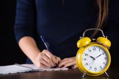 Αναδρομικές κίτρινες ηλικιωμένες ρολόι και γυναίκα στο γράψιμο υποβάθρου στοκ φωτογραφία