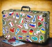 Αναδρομική βαλίτσα με τις αυτοκόλλητες ετικέττες στο πάτωμα στοκ φωτογραφία