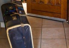Αναδρομική βαλίτσα χαρτονιού έξω από μια ανοιχτή πόρτα Στοκ εικόνα με δικαίωμα ελεύθερης χρήσης