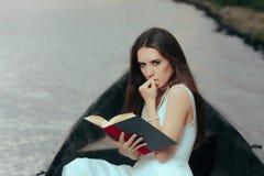Αναδρομική γυναίκα που διαβάζει ένα βιβλίο σε μια εκλεκτής ποιότητας βάρκα στοκ φωτογραφία