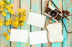 Αναδρομική κάμερα και κενό παλαιό στιγμιαίο λεύκωμα φωτογραφιών εγγράφου στον ξύλινο πίνακα με το σχέδιο συνόρων λουλουδιών Στοκ φωτογραφία με δικαίωμα ελεύθερης χρήσης